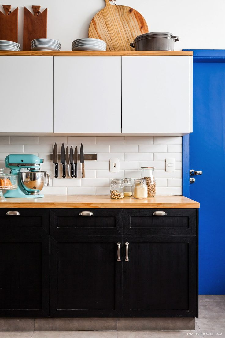 Subway tiles, madeira clarinha, armários em preto e branco e porta azul royal nessa cozinha industrial.