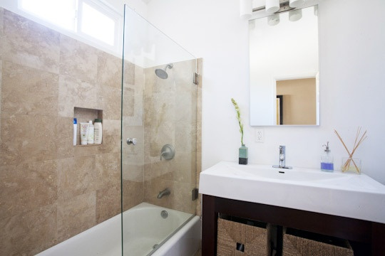 vanity next to tub with glass shower wall divider