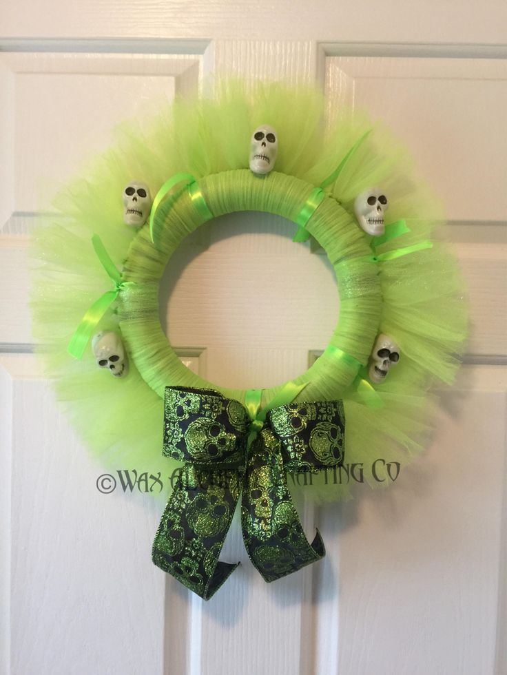 Halloween Tulle Wreath is a cute yet spooky home decor wreath for Halloween or use all year around! Perfect 12 inch size on a foam wreath frame this wreath has fall green colored ribbons and tulle and glittered tulle. Handmade metallic glittered black and green bow with plastic