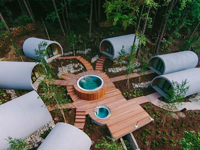 L'espace bien-être est délimité par un muret de rondins de bois et un portillon d'accès automatisé. Au centre, une plage en bois épouse la déclivité du sol et accueille un spa et un bassin d'eau froide, tous deux en inox. Les vestiaires et l'espace détente, à droite, font face au hammam et aux trois saunas.