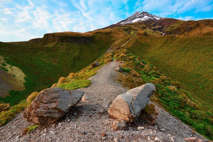 A pathway along a ridge leading up a mountainside with the peak of Mt Taranaki in the distance, Egmont National Park