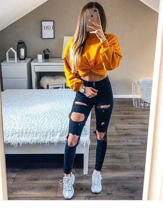 junges Mädchen, das blaue zerrissene Jeans, gelbe…