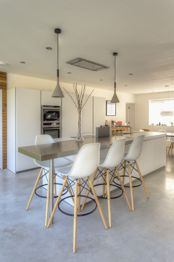Minimalism done to perfection: The synergy between the poured concrete floor, white laminate island, stainless steel fly-over breakfast bar and wood accents is palpable. Kitchen by bulthaup Winchester