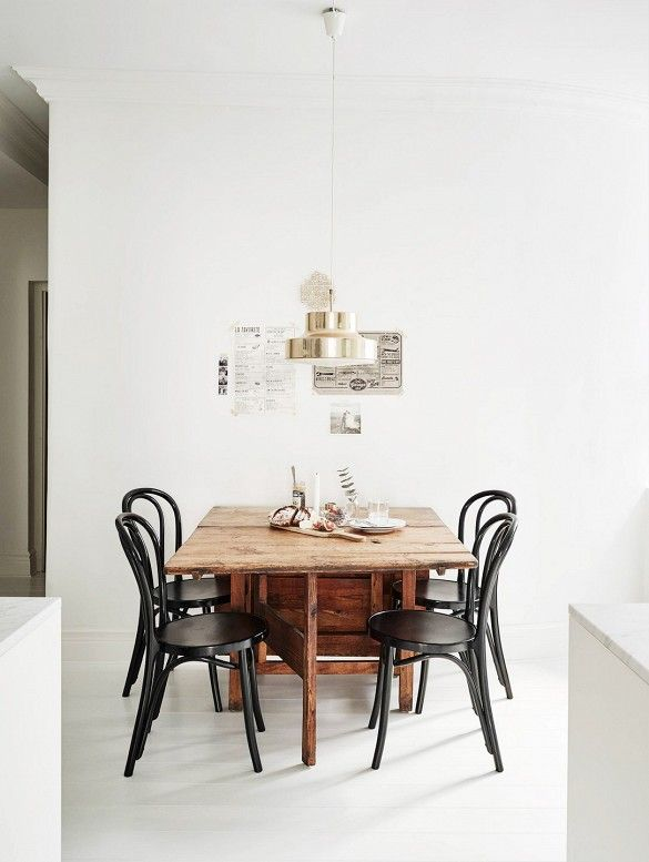 Minimal dining space with white walls, wood table, black chairs, a modern light fixture, and tiny gallery wall #smalldiningroomideas #diningroomdecoration #diningroomideas #diningareadesign dining room design, dining room decor, modern dining room | See more at diningroomideas.eu