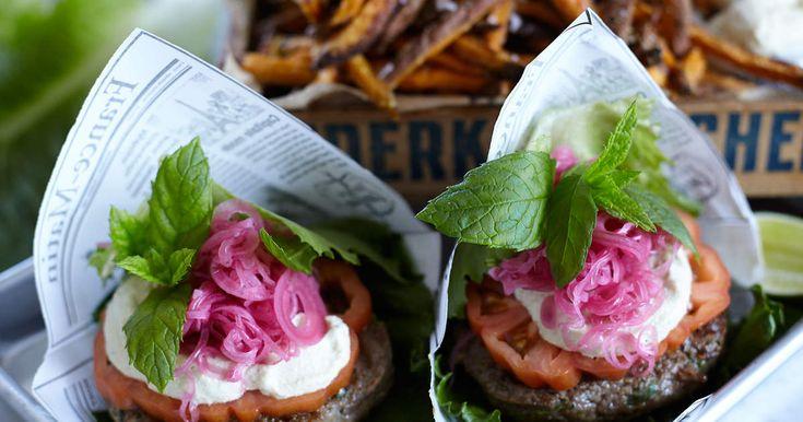 Servera hönsburgaren i isbergssalladsblad med cashewmajonnäs och picklad rödlök tillsammans med sötpotatispommes.