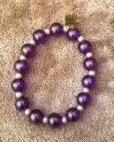 5001 : armbandg van paarse glitter kralen met ertussen enkele goudkleurige parels en kleine champagne kleurige kraaltjes  €4,00