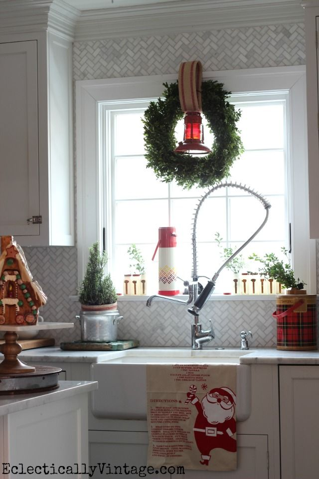 Festive Christmas kitchen window - love the old lantern in the wreath and the thermoses - part of this beautiful Christmas home tour eclecticallyvintage.com