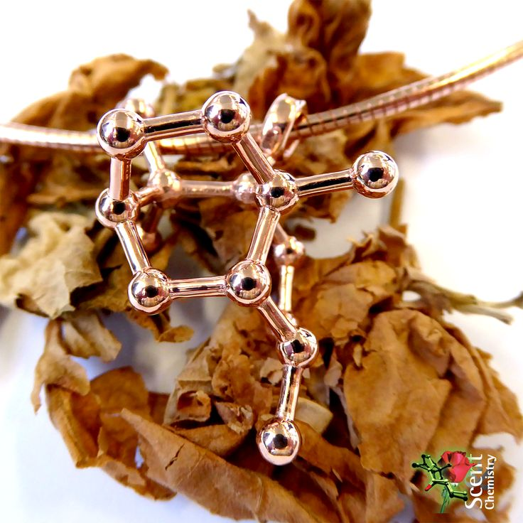 Rose gold plated Patchoulol molecule jewelry on a heap of dried fermented patchouli leaves. With a content of 23.6–45.9% (–)-patchoulol is the main constituent of patchouli oil, and despite some debate today generally recognized as its smelling principle. An iconic hallmark for an alternative or bohemian lifestyle and a mysterious lucky charm.