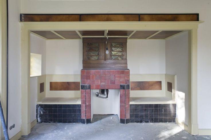 Interieur, woonkamer met betegelde schouw met een sigarenkastje daarboven en zitbankjes aan weerszijden van de haard tijdens verbouwing - Boxtel