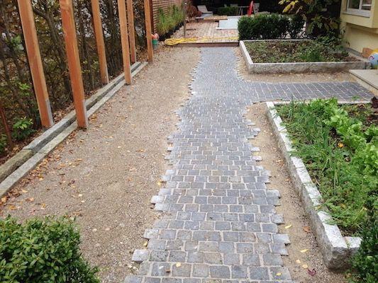 Weg aus dunklem Granit mit ausgefransten Rändern, wassergebundene Decke und mit Granit eingefasste Gemüsebeete 20cm erhöht.