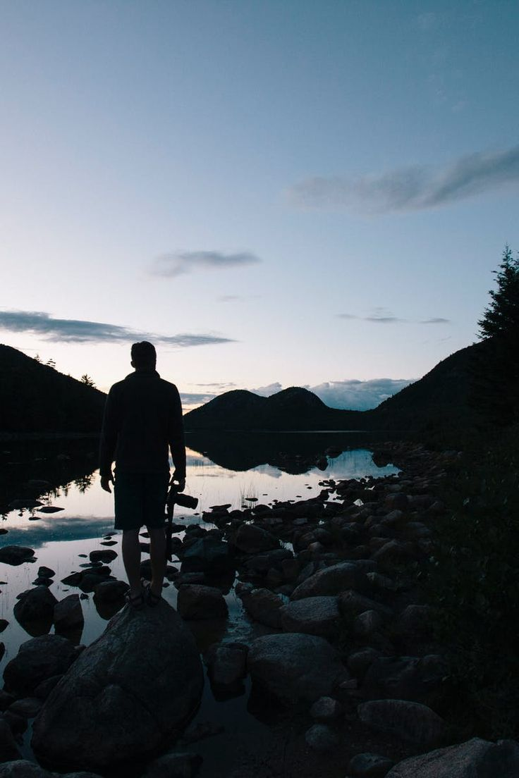 Silhouette of Man Near Body of Water Near Silhouette of Trees and Mountains