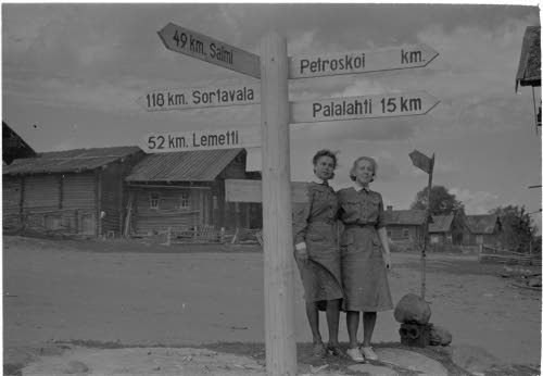 Lotatkin katselevat jo toivorikkaina Petroskoin tienviittaa.  Kolatselkä 1941.08.19. SA-kuva.