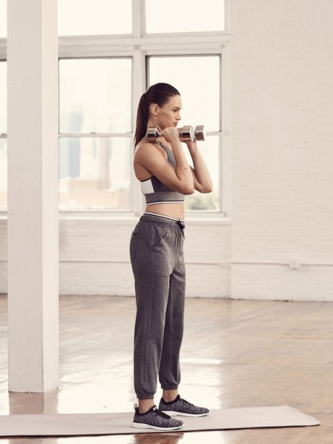 Slide 5 of 6: <p><strong>1. </strong>Stand with feet a little more than hip-width apart, holding dumbbells on tops of shoulders. </p><p><strong>2.</strong> Lower into a deep squat. Stand and press dumbbells overhead. Repeat. </p>