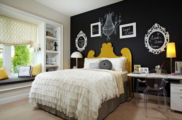 Empty picture frames and chalkboard paint create a vibrant accent wall in the bedroom