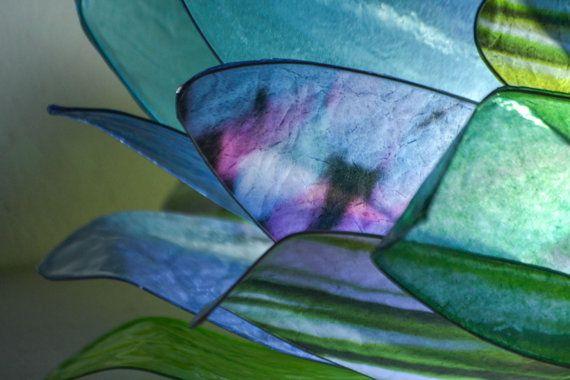 Magiche emozioni suscita questa lampada Bocciolo creata sui toni del blu, verde e viola.  La lampada è interamente realizzata a mano utilizzando un procedimento, che attraverso lapplicazione della resina, crea delle bellissime trasparenze e conferisce ai petali un aspetto vetrificato e resistente.  La lampada è stata disegnata per poter essere facilmente collocata in qualsiasi ambiente, puó essere appesa, appoggiata, come preferite.  Il cavo é ricoperto da nastro di raso azzurro ed é…