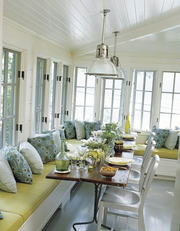 Casement windows wrap the dining room, providing wide-open views of the lake. Navy chairs from Design Within Reach. Mitchell Gold + Bob Williams pillows. Early-20th-century French factory lights from R.T. Facts. Glassware on the farm table is from Source Perrier.