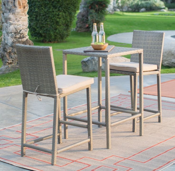 Stylish 3 piece outdoor wicker bar height patio set features all weather wicker small space balcony seating with counter height chairs with padded cushions.