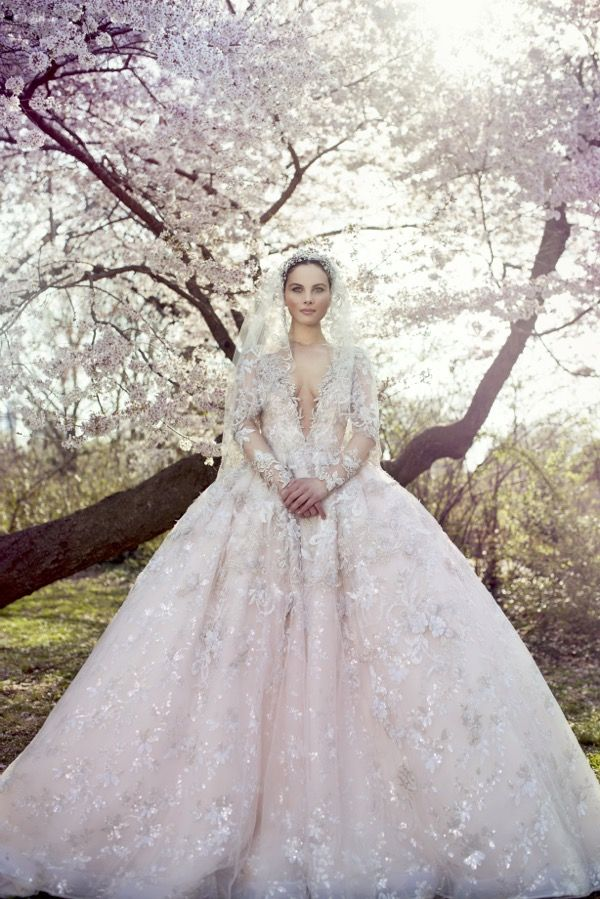 Ysa Makino Bridal Collection - Beautiful Designer Wedding Dresses - A deep V-neckline wedding dress in princess skirt silhouette with gemstones embellishment,sequins motifs and lace appliques on the bodice cascading to the skirt. Neckline, back and long sleeves in sheer appearance.