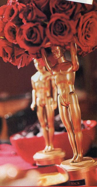 "Hollywood Theme Oscar Centerpieces - looked this up! Spray paint gold the ken barbies(dollar store) and hot glue them to a tuna can. Use them to hold flower ball!    Could be used for ""Oscars"""