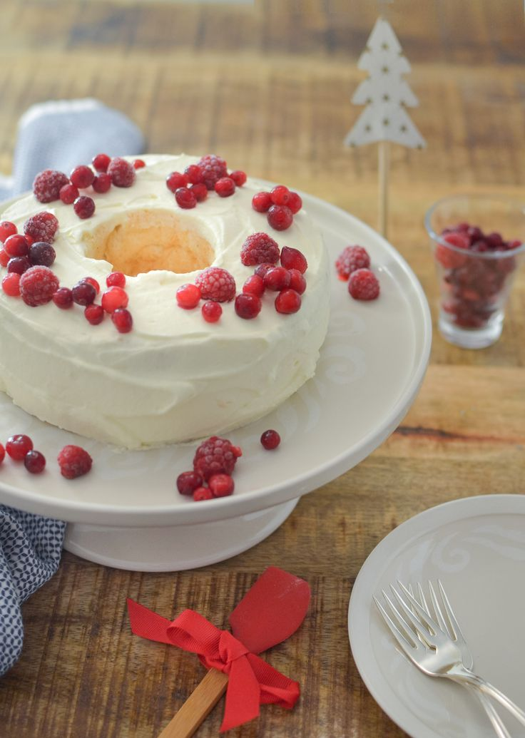 Gluten Free Angel Cake, topped with whipped cream, raspberries and cranberries