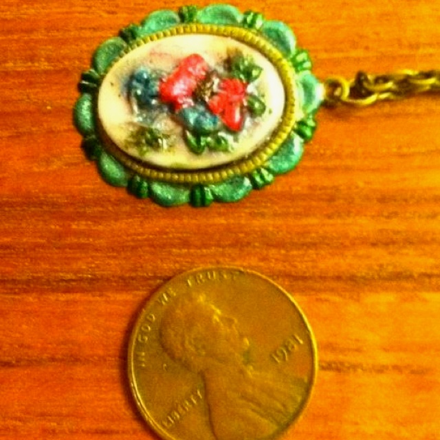 A pendant on a chain of a necklace with an enameled box clasp. The brass setting is enameled, and the cameo set in the setting is enameled. The cameo is made with resin.