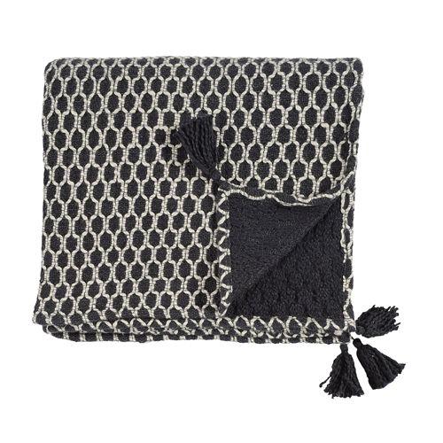 Plaid en coton tissé noir avec motif beige Jardin d'Ulysse.  Agrémenté de pompons à ses extrémités, ce plaid fera son effet posé sur votre canapé, ou sur un lit parental.