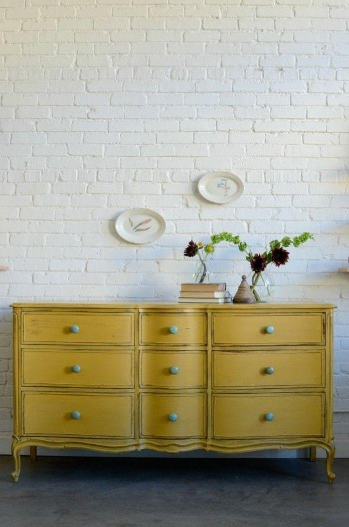 une ancienne commode couleur jaune moutarde en contaraste avec le mur en briques blanches