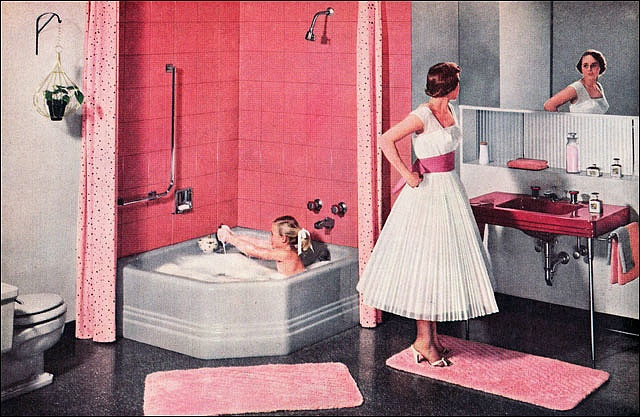 1956- Wow this woman has got it together! Look at her pristine white dress while she bathes her child!