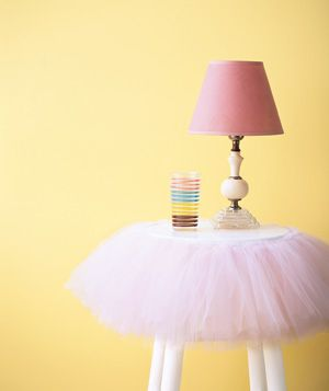 Create an enchanting nightstand from a kitchen stool by wrapping a tutu around the edge of the seat and securing it with double-sided tape.