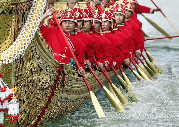 Thai Royal Navy oarsmen, in ancient warrior costumes, row the royal barge in a ceremonial procession on the Chao Phraya River in Bangkok