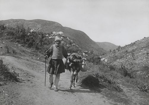 An elderly man and his donkey travel along a Greek mountain road. 1900s. Location: Peloponnesus Peninsula, Greece. Photographer: FRED BOISSONNAS/National Geographic Creative
