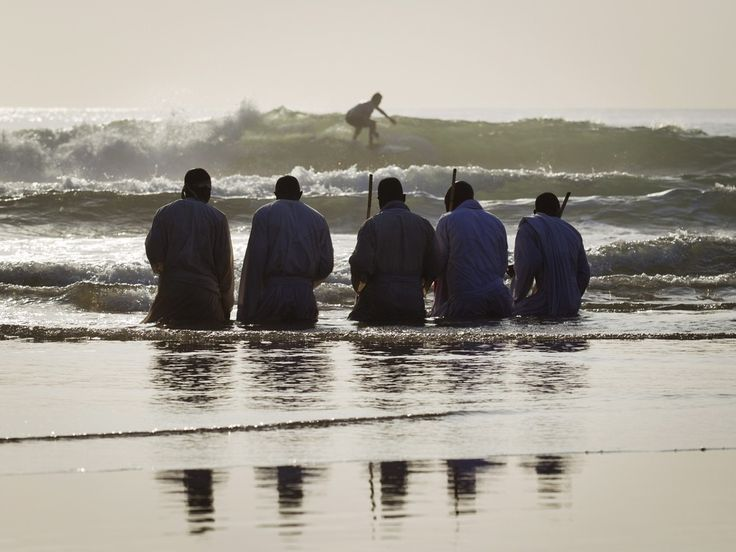 Members of the Shembe church kneel in the sea while praying as a surfer rides a wave in the background Photograph: Rogan Ward/ Reuters