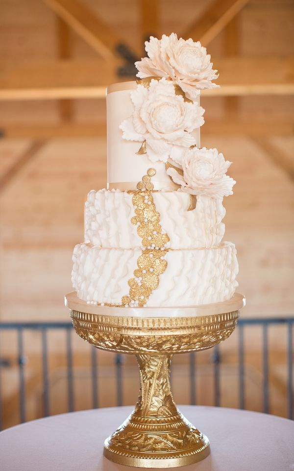 Amy Cakes created an opulent three-tiered cake blanketed in ivory fondant ruffles; embellished with gold sugar medallions and sugar pearls; and topped with handmade sugar peonies. An ornate gold pedestal enhanced the presentation.