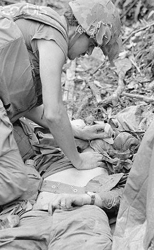 13 Jun 1968, Khe Sanh, South Vietnam --- Khe Sanh, South Vietnam: Navy medic, Gene Holtman of Tell City, Indiana prepares to give mouth-to-mouth resuscitation to a wounded leatherneck. The Marine of the US 3rd Marine division, was injured when an American fighter plane accidentally bombed an allied position during Operation Scotland II. One Marine was killed and nine others injured.