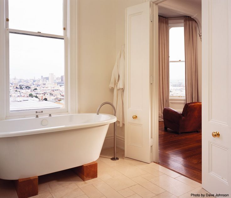 Scandinavian bathroom with a freestanding bathtub, tall double doors and tub raisers. A great way to save money is by adding a shower to this freestanding tub. See how...