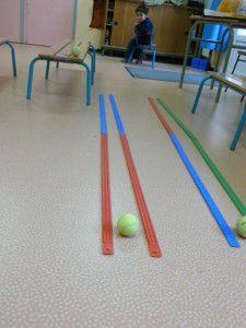 Tussen 2 dikke lijnen (?) een tennisbal laten rollen. Concentreren maar!