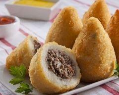 Coxinha (croquette brésilienne à la viande hachée) - 2 pommes de terre cuites vapeur et réduites en purée - 300 g de farine - 48 cl de lait - 24 cl d'eau - 1 c. à soupe de beurre - 2 cubes de bouillon de volaille Pour la farce : - 1,5 kg de viande de boeuf hachée - 1 oignon - 2 gousses d'ail - 3 c. à soupe de fromage à la crème - 2 c. à soupe d'huile - sel, poivre Pour la finition : - 2 oeufs battus - chapelure - huile pour friture