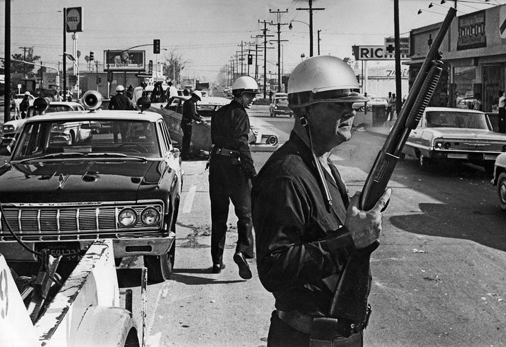 Los Angeles police officers stand guard as debris is cleared from the intersection of Avalon Boulvard and Imperial Highway during the Watts riots, photographed by Ray Graham for Los Angeles Times (August 13, 1965).