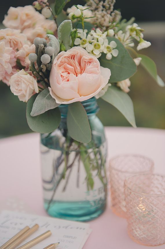 The cocktail tables will feature a clear hobnail jar filled with bay laurel, seeded eucalyptus, dusty miller, and blush spray roses