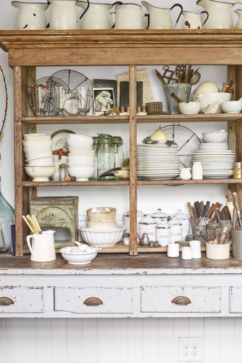 """""""This shelf, one of the first pieces we bought for the farmhouse, sits on top of a worktable. It's where I keep my ironstone dishes,"""" says the homeowner. These shabby chic pieces and open shelving add farmhouse style to the home."""