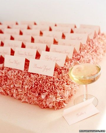 The most classic fold used on seating cards is brought to new heights when seating assignments rest on top of a pillow of carnations. Cut several standard bricks of floral foam in half horizontally, soak in water, and place in shallow plastic flower-box trays. Snip off the carnation heads, leaving a little bit of stem on each, and insert into the foam; each half-brick should hold about two dozen carnations and four seating cards.