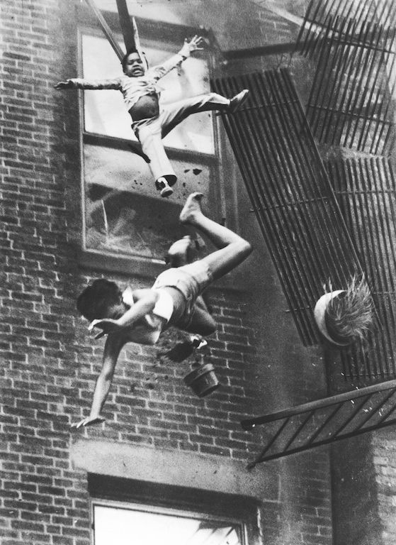A mother and her daughter are hurled off a collapsing fire-escape in an apartment house fire in Boston. (Stanley Forman) 1975