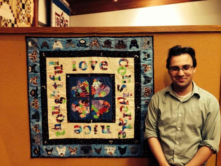 Curator Ben Justman with the fabric quilt.