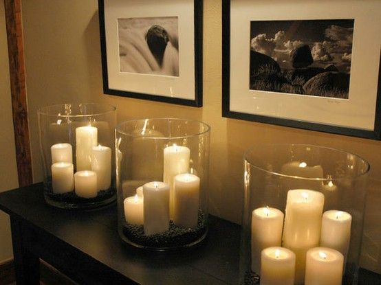 Big lighting bang-for-the-buck Dollar-Store pillar candles and hurricane glasses. Add a red ribbon around the outside. Love this look!
