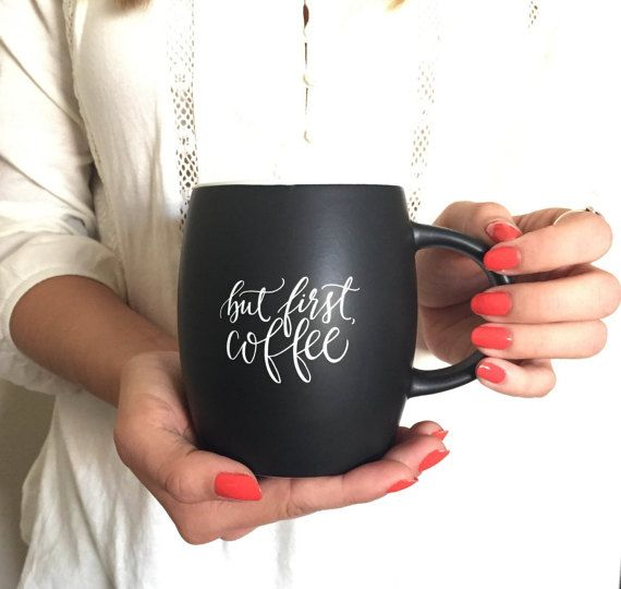 One of the Printable Wisdom specialty mugs - But First, Coffee Printed in white ink on a matte black surface. The inside and rim of the mug are a