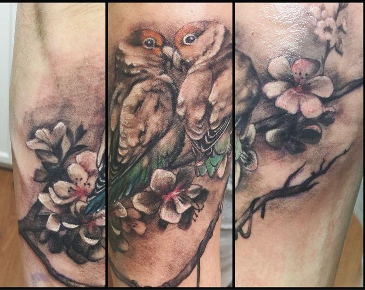 Tatuaje agapornis sobre rama de almendro