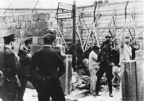 1677 1962/5/27 Onbekenden hebben in de Berlijnse Muur ter hoogte van de Bernauerstrasse met springstoffen een gat geblazen. Foto: Terwijl VOPO's (achter grond) en West-Berlijnse politiemannen (voorgrond) als kemphanen tegenover elkaar de wacht houden, maken metselaars het gat dicht F: onbekend