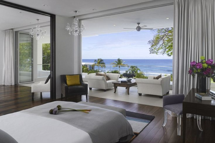 Large floor-to-ceiling windows in the hibiscus suite bedroom roll back to reveal views of ...