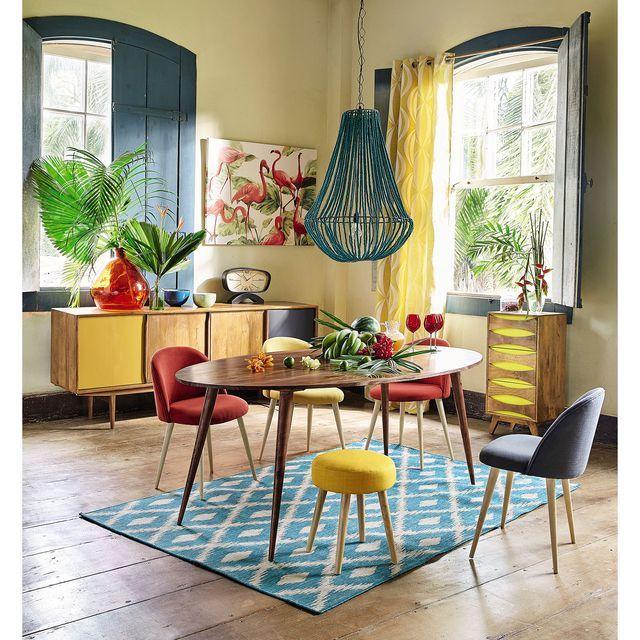 Salon coloré avec des plantes tropicales et une table ronde en bois