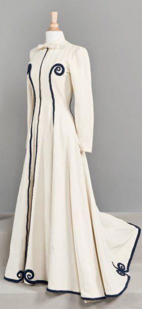 Manteau long blanc , à manches longues et petite traîne. Liseré et motifs  bleu marine  le long de l'ouverture et du bas. Application bleu marine sur le devant .Balenciaga 1938-40
